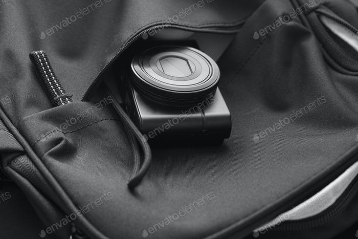 Compact camera inside a backpack. Black and White.