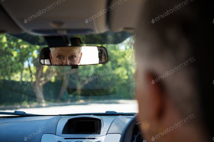 Senior woman looking into rear view mirror while driving a car