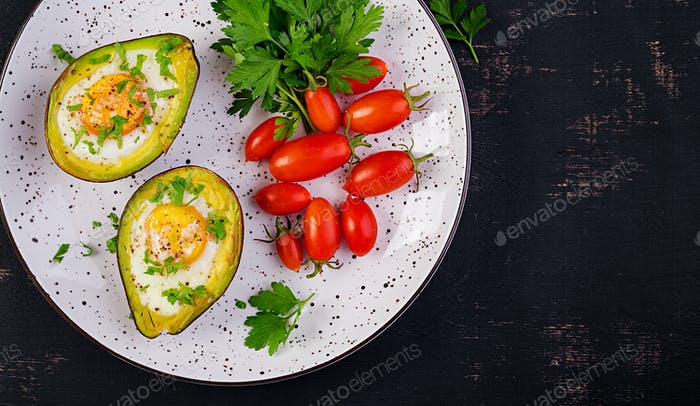Avocado baked with egg and fresh salad. Vegetarian dish. Top view, overhead.  Ketogenic diet