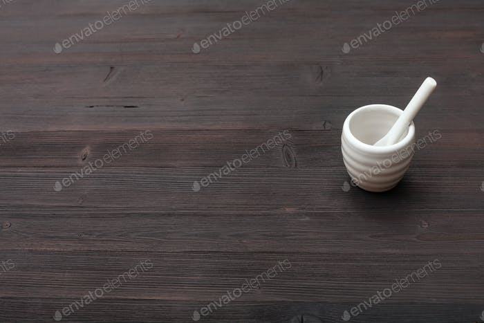 cup for sake with spoon on dark brown wooden board