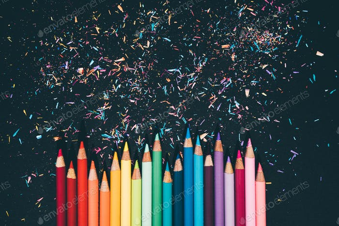 Colorful pencil and pencil shavings on black background.