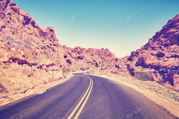 Retro stylized deserted canyon road, Nevada, USA.