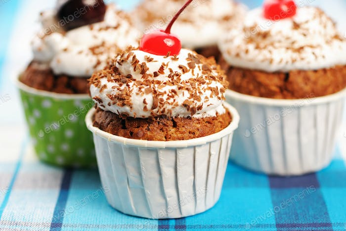 Cupcakes with whipped cream and cherry