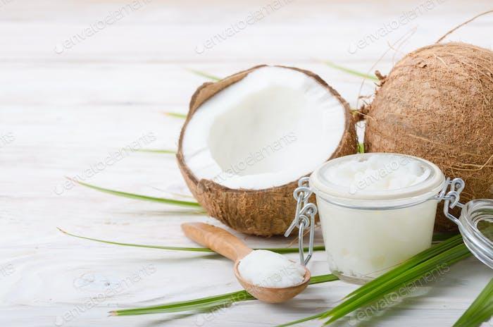 Kokosöl in luftdichtem Glas Löffel und Muschelstücke auf Whit
