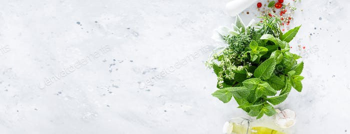 Bunch of aromatic herbs in mortar on kitchen table. Banner