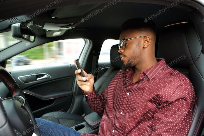 junge afrikanische amerikanische Mann Blick auf Handy vor dem Autofahren im Auto