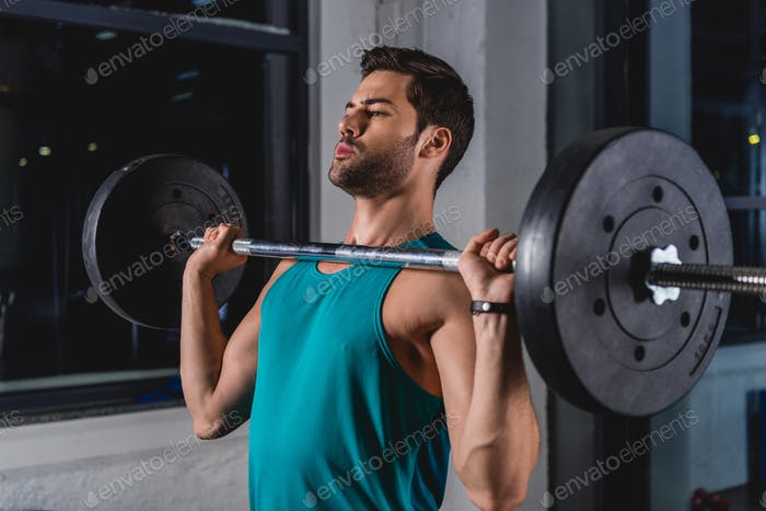 sportsman lifting barbell in sports hall