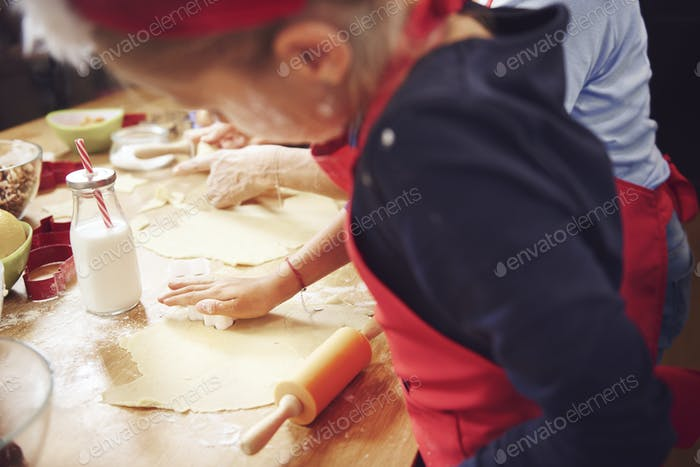 Cute grl using a cookie cutter while baking