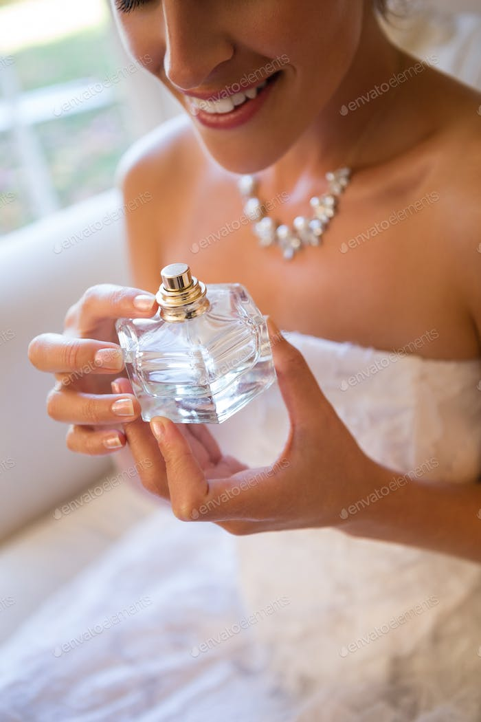 Midsection of smiling bride holding perfume sprayer while sitting on armchair