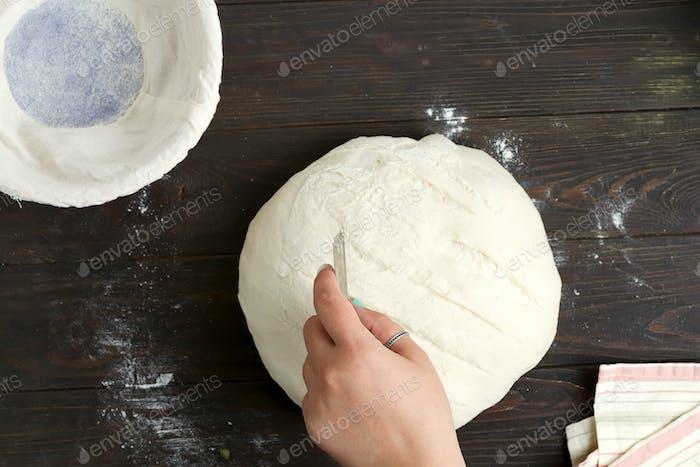 Frauen-Hand schmückt frisch zum Backen hausgemachtes gesundes Brot auf einem Holz dunkel zubereitet