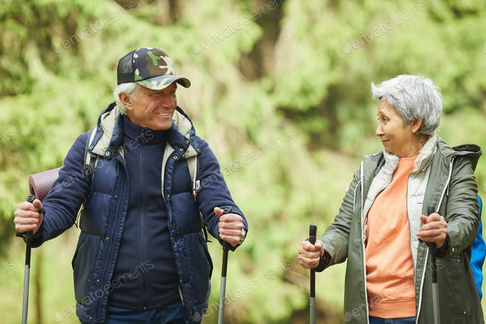 Senior Couple Enjoying Nordic Walk in Forest