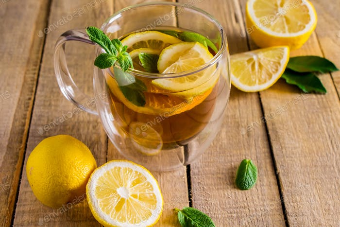 Tea with lemon and mint in transparent cup. Alternative medicine. Hot drink for relaxation.