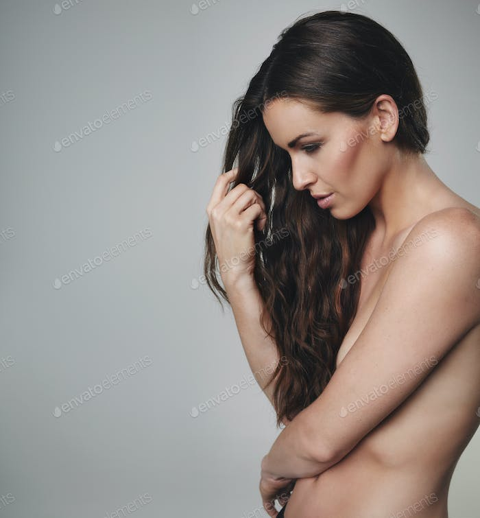 Natural beauty with long hair standing topless