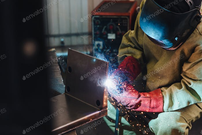 Industrial worker or welder wears protective mask and gloves erects technical steel on factory