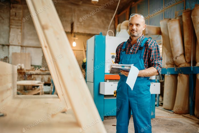 Carpenter with notebook, wood processing, factory