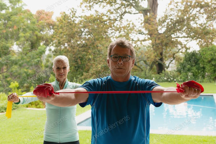 Front view of active senior Caucasian couple exercising with resistance band in porch at home