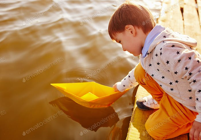 Little boy playing with toy paper ship by the lake