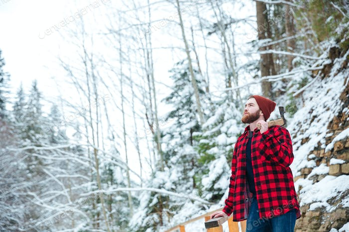 Man in checkered shirt with axe standing at winter forest