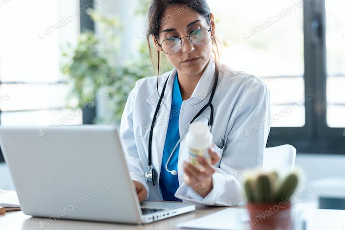 Concentrated female doctor writes the medical prescription in a laptop in the consultation.