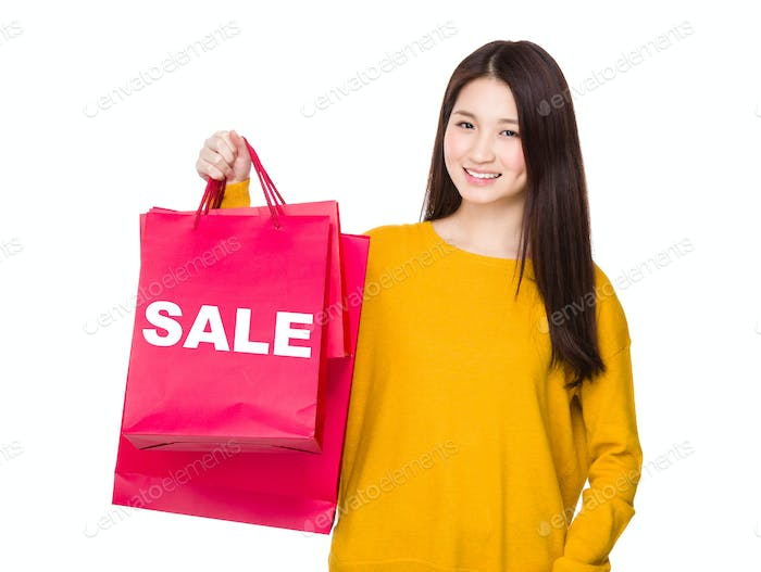 Woman hold with red shopping bag and showing a word sale
