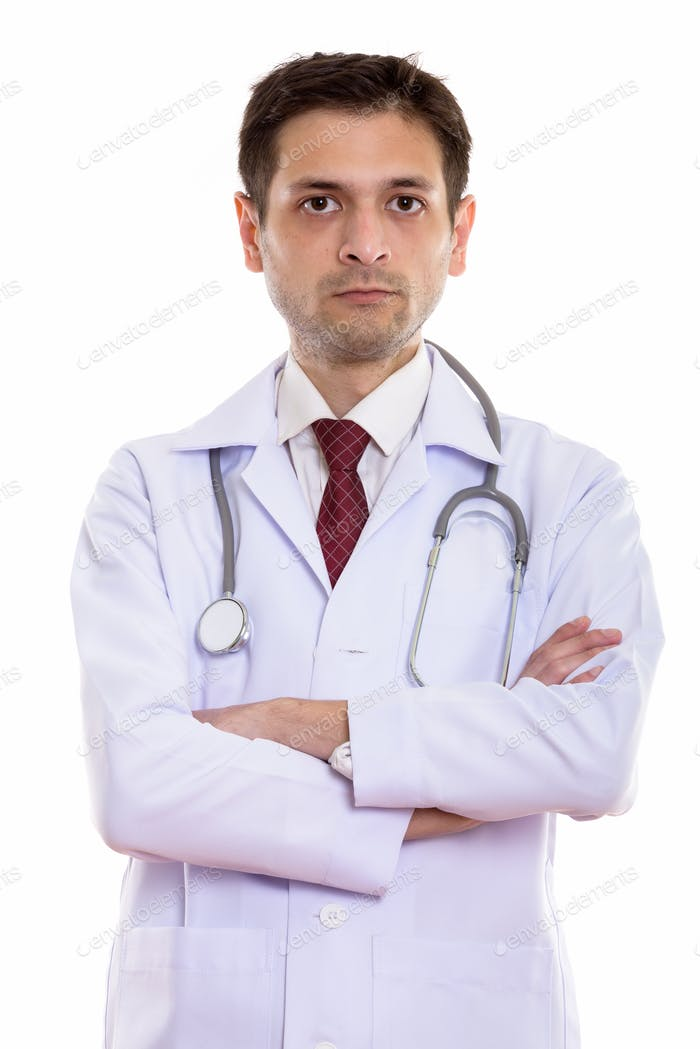 Studio shot of young man doctor with arms crossed