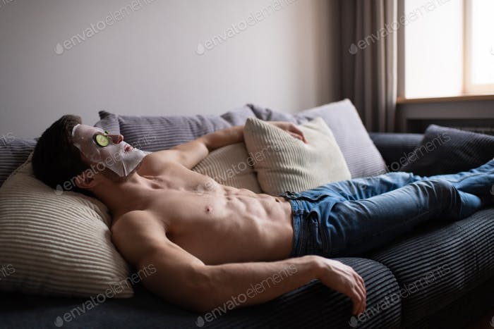 Man in skincare mask relaxing on sofa