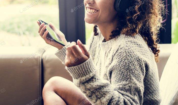 Frau genießen mit ihrer Musik auf einem Sofa