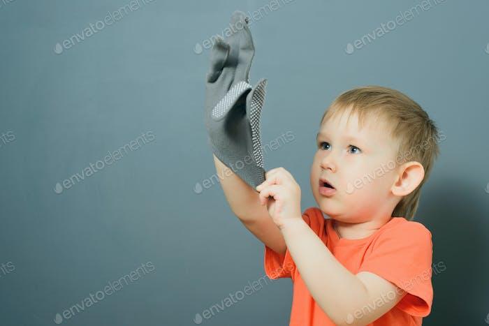 baby boy puts on gloves