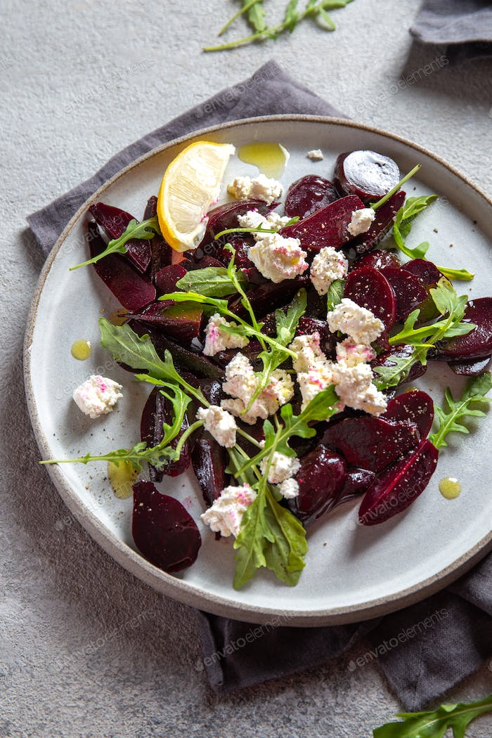 Beetroot cheese salad carpaccio with arugula and lemon.