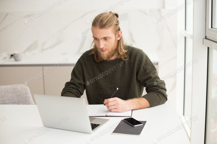 Young man sitting with laptop and making notes in notebook at home