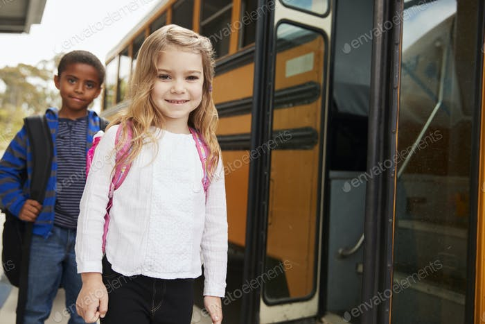 Elementary school girl and boy waiting to board the school bus