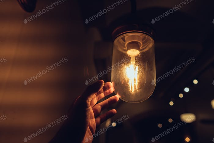 Hand reaching for a vintage light bulb
