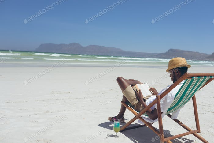 Young man holding book while sitting on sun lounger at beach on sunny day
