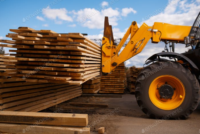 Forklift loads the boards in the lumber yard