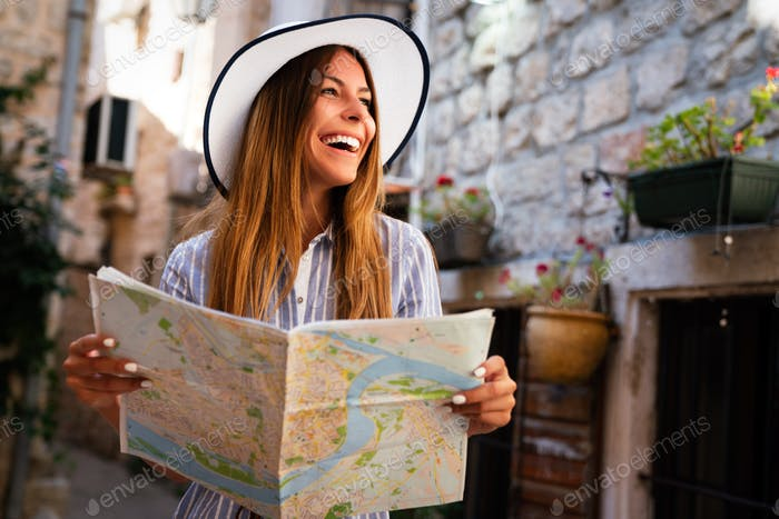 Happy young woman with map in city. Travel tourist people fun concept