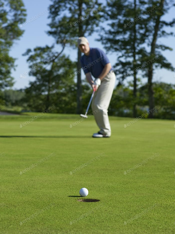 Golfer Putts on Green with Focus on Ball and Hole