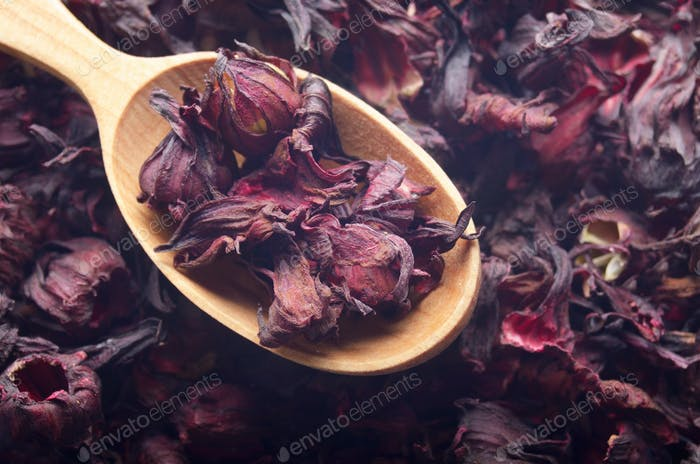 Top view of Dry Hibiscus petals in wooden spoon background close