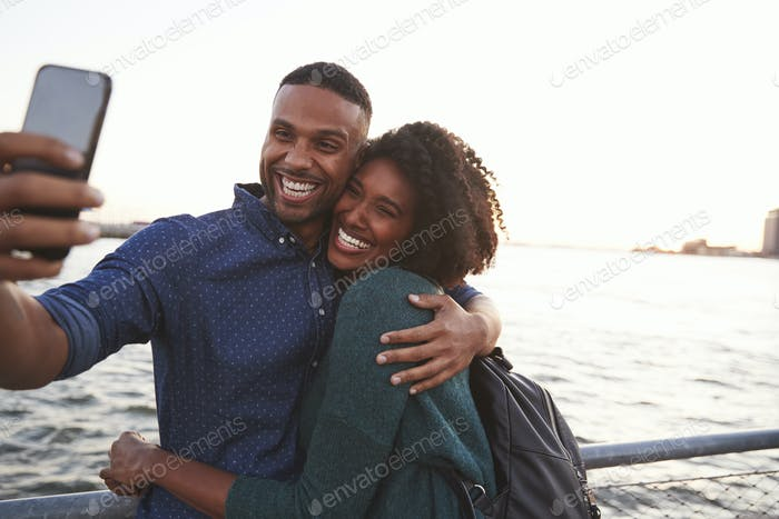 Young black couple taking photo on quayside, front view