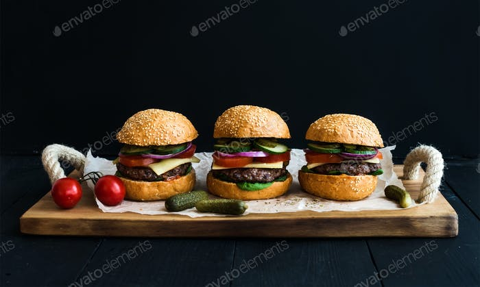 Fresh beef burgers on paper over rustic wooden tray, black background.