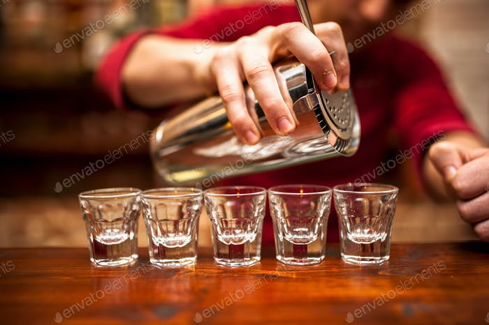 Close-up of bartender hand pouring alcoholic drink in nightclub,