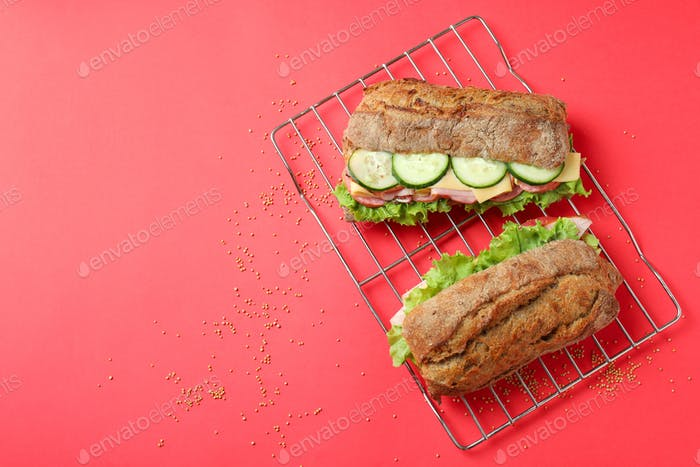 Baking rack with ciabatta sandwiches on red background