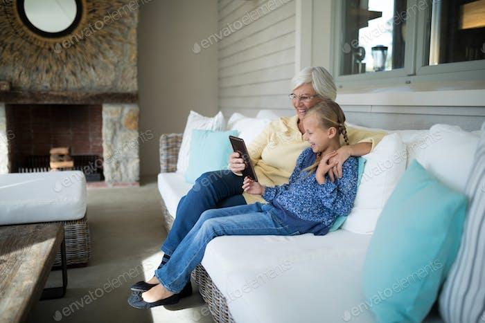 Smiling granddaughter and grandmother using digital tablet on sofa