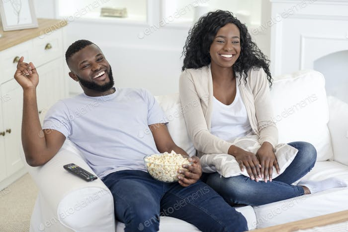 Cheerful millennial couple watching comedy movie on tv