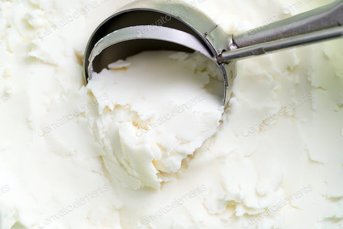 Vanilla natural ice-cream scooped out from container with freshly cooked dessert