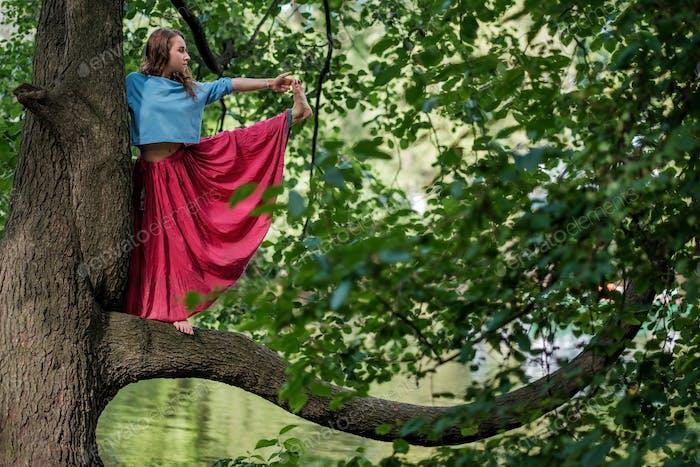 Caucasian woman standing in yoga balance Utthita Hasta Padangusthasana pose. She hold trank of tree