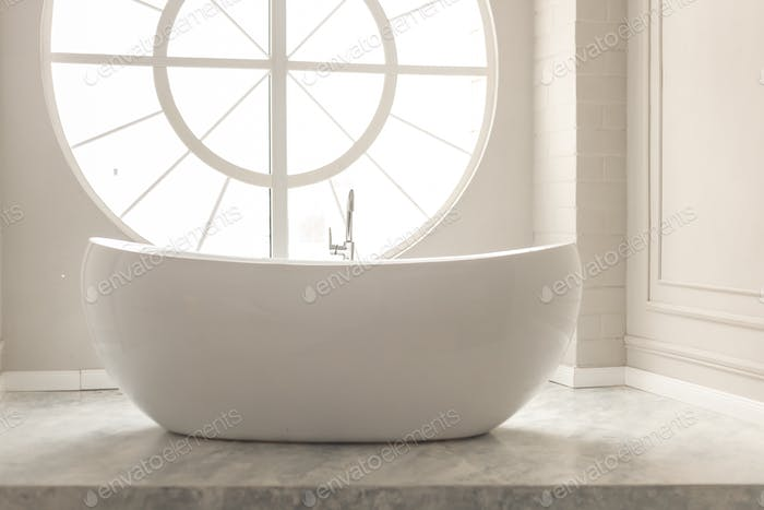 White modern floor bathtub with round window and pastel painted walls with stucco
