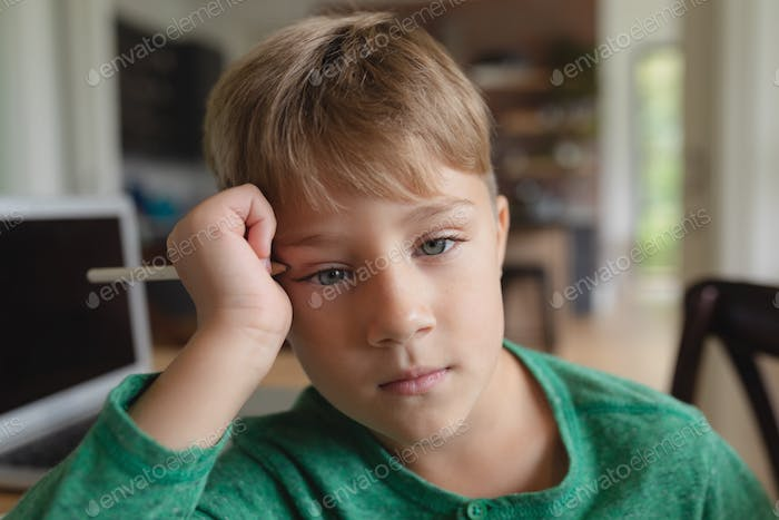 Close-up of cute Caucasian boy with hand on head looking at camera in a comfortable home