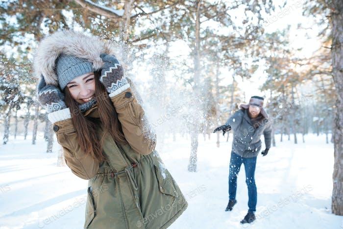 Schöne glückliche paar werfen Schneebälle und Spaß haben