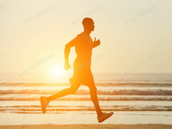One man running on beach with sunset