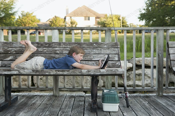 A young boy outdoors lying on a bench using a digital tablet. fishing equipment.